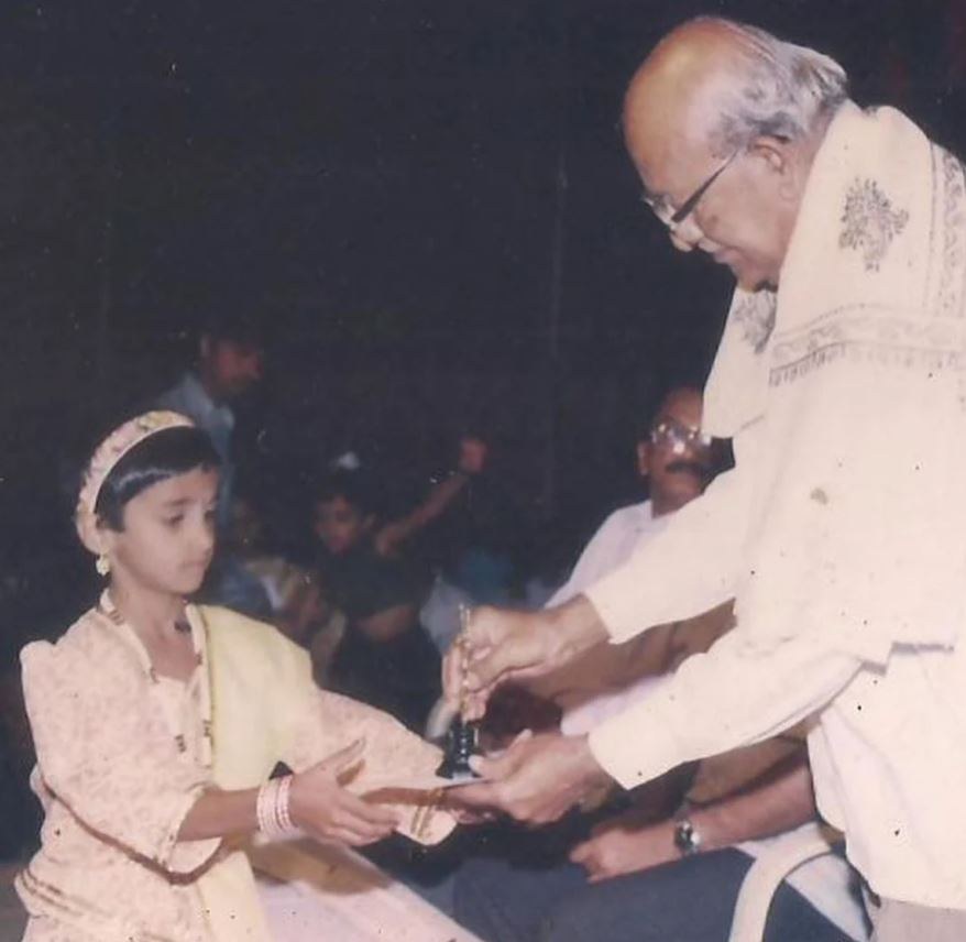 An old photo of preteen Divya Uruduga receiving an award for her performance at the school's annual function.